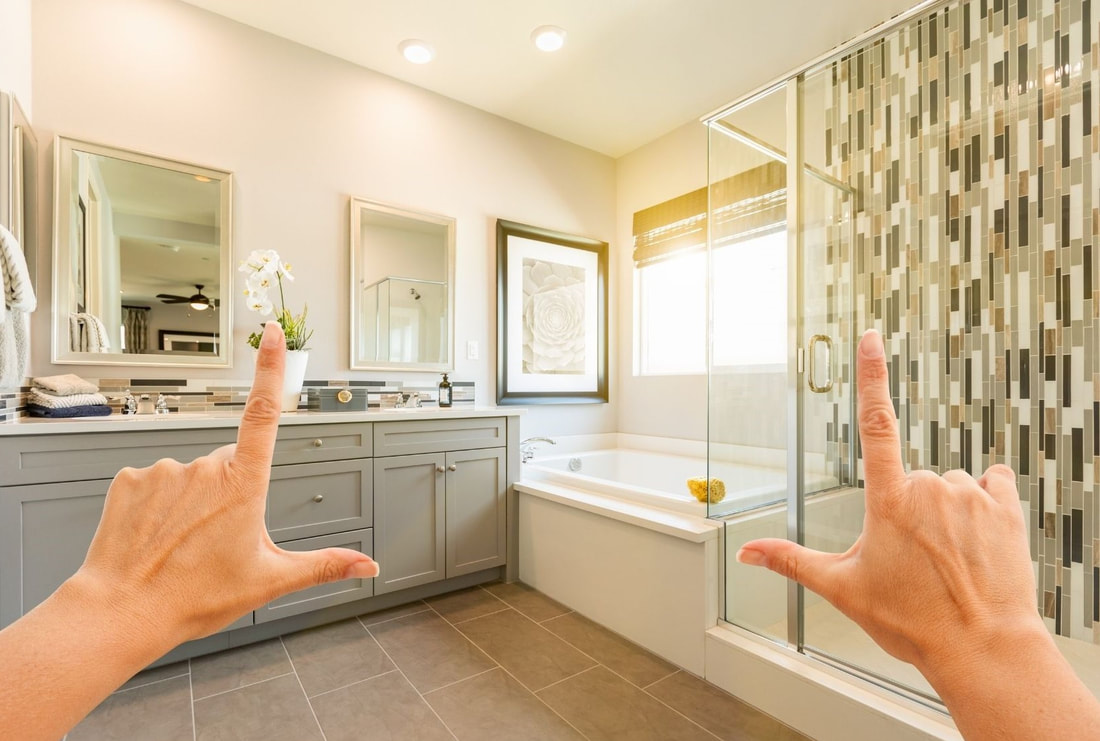 Picture of a remodeled bathroom with two hands forming the shapes of L's symbolizing a imaginationThe colour theme of the bathroom is grey. picture frame.