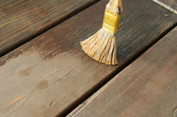 Picture of a paint brush apply deck sealer on a brown wood patio.