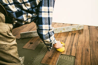 Laminate floor installation picture of a handyman installing brown hardwood holding a level and wet sponge.