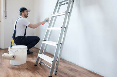 Handyman painter picture of a worker in blue overalls and white T-shirt painting a wall blue with a roller. The worker is kneeled down crouched beside his painting tools and step ladder.