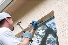 Maple Ridge Window Installer holding a crow bar to a exterior window. The worker is preparing to hit the crow bar with a hammer to remove the window for a retrofit window replacement and installation. The worker is wearing a white backwards hat and white T-shirt with blue and grey gloves.