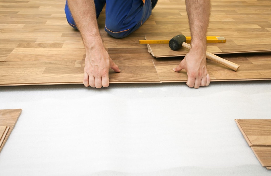 Picture of a handyman installing laminate floor. The floor installer is on his hand and knees' inserting a plank wearing blue pants.