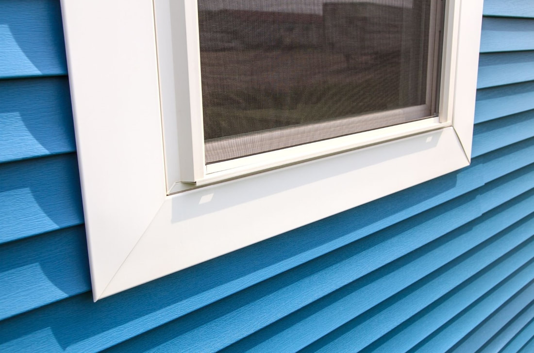 Picture of a new replaced vinyl white window with blue siding.